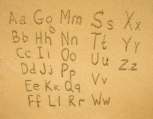 Alphabet written on a sand beach.
