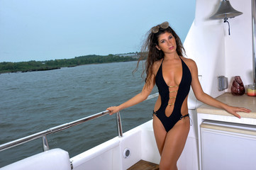 Sexy young woman in one piece swimsuit posing on the yacht.