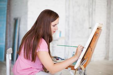 woman paints picture on canvas