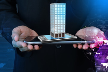 Smart hand showing smart phone with real estate concept