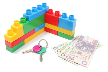 Wall of plastic building blocks with home keys and money