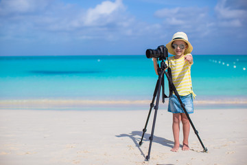 Little girl shooting with camera on tripod during her summer