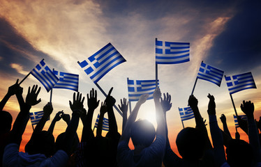 Silhouettes of People Holding the Flag of Greece