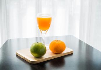 Glass of freshly pressed orange juice with two orange