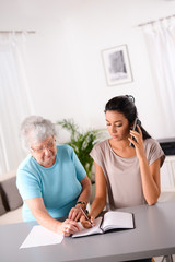 young woman helping old person for paperwork and telephone call
