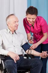 Nurse measuring blood pressure of disabled