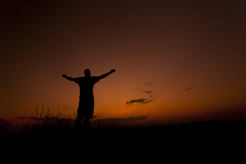 Man worshiping with his hands up in the sunset sky