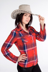 Girl in a cowboy hat and plaid shirt, hat holding hand
