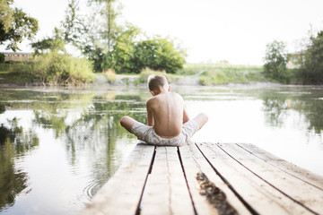 Boy sitting at the lake