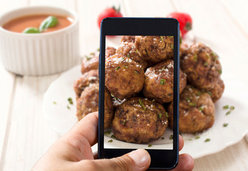 Man shooting with his cell phone camera meat balls