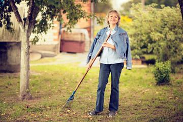 Mature woman raking leaves in her garden.