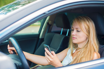 Beautiful young woman writing sms while driving car.