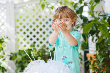 Happy little boy making experiment with colorful water and soap