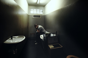 One man on a bed of a small room of a prison