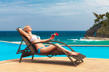 Young woman laying at the tropical beach and enjoying cocktail.
