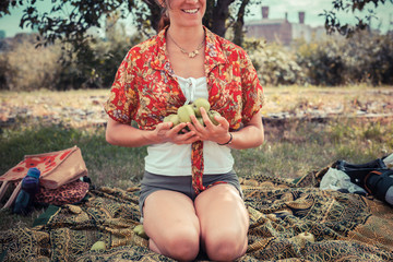 Young woman outside with apples