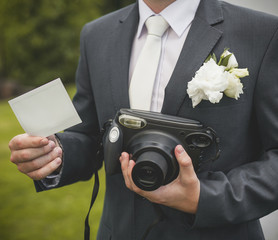 Part of groom with retro camera and empty card