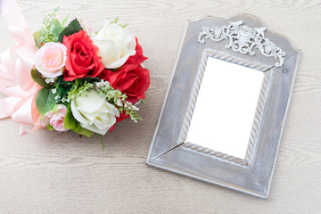Wooden frame with white space beside rose bouquet
