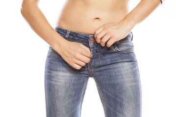 women zipping her jeans on white background