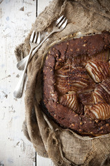 pears and dark chocolate tart on rustic vintage background