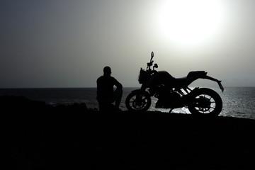 Hombre Sentado Junto A Su Motocicleta