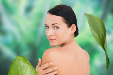 Beautiful nude brunette posing with green leaves