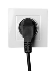 black cable plugged in a white electric outlet isolated