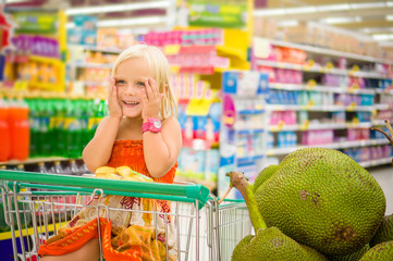 Adorable girl in shopping cart looks at giant jack fruits on box