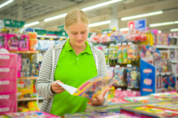 Young mother select kids books in supermarket