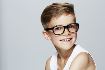 Portrait of young boy wearing glasses, studio.