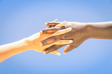 Interracial human hands crossing fingers for friendship and love