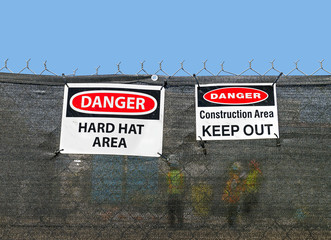 Construction site signs. Workers barely visible through fence.