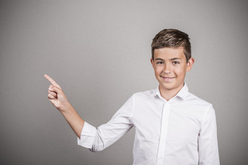 Happy teenager pointing at blank copy space grey background
