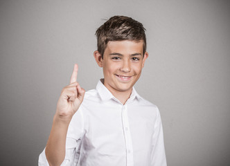 Happy young man pointing with finger up, number one