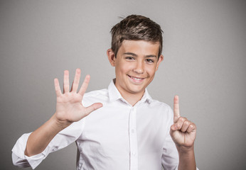 Handsome teenager showing 6 fingers, palm, number six gesture