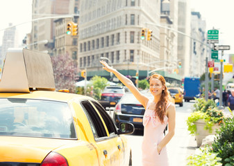 Happy woman hailing taxi cab in Manhattan New York city