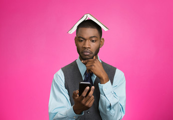 Man holding mobile phone, book over head, pink background