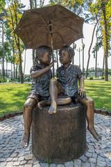 Sculpture boy and girl under an umbrella
