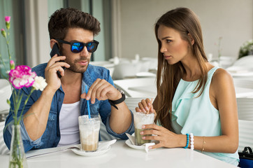 Handsome man with beautiful woman in cafe talking by the smartph