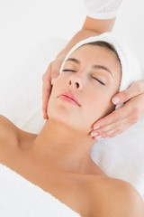 Attractive young woman receiving facial massage at spa center