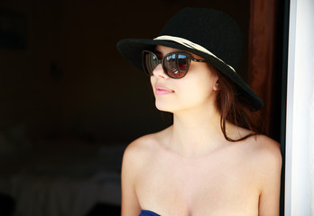 Portrait of a happy woman in hat and sunglasses looking away
