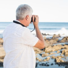 Casual mature man taking a photo of the sea
