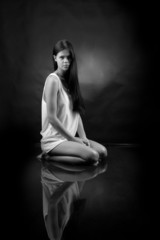 Girl in a white shirt sitting in water on a black background.