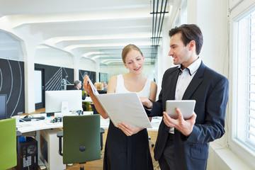 Geschäftsfrau fragt Kollegen um Rat im Büro