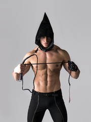 Scary muscular young man with pointed hood on naked body