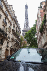 Eiffelturm mit Auto und alten Häusern im Vordergrund