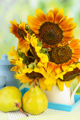 Beautiful sunflowers in pitcher with pears