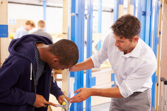 Teacher With Student In Carpentry Class Fitting Door Lock