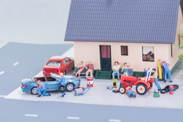 Miniature mechanics repairing a car and a farm tractor