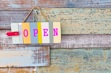Open sign board on wooden vintage background